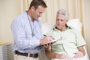 Physician checking a chart and speaking to a senior patient