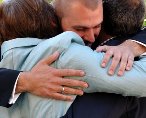 Man hugging family to celebrate cancer remission