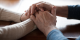 Cancer patient and cancer caregiver holding hands