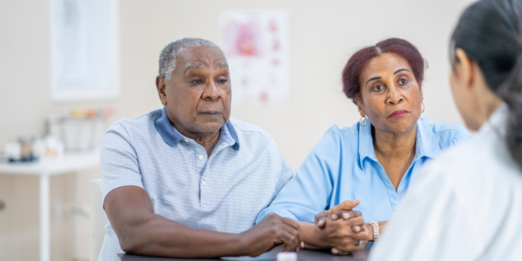 Couple discussing cancer treatment options with doctor